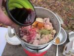 Закладываем куски курицы, добавляем соль, специи, двести грамм красного вина